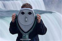 Man looking through coin-operated binoculars, Niagara Falls in background Stock Photo - Premium Royalty-Freenull, Code: 6106-06988165
