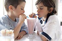 preteen long hair - Two boys (6-10) sitting at cafe sharing milkshake Stock Photo - Premium Royalty-Freenull, Code: 6106-06989111