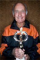 Senior man holding sports trophy Stock Photo - Premium Royalty-Freenull, Code: 6106-06989198