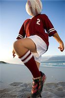 Boy (12-13) playing football on beach, ball obscuring face Stock Photo - Premium Royalty-Freenull, Code: 6106-06989211