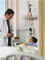 Mature doctor talking to patient in bed Stock Photo - Premium Royalty-Freenull, Code: 6106-06989855