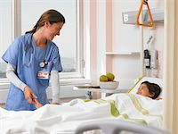 Doctor talking to girl (5-7 years) in hospital bed Stock Photo - Premium Royalty-Freenull, Code: 6106-06989857
