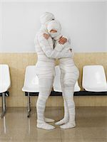 Couple wrapped in bandages embracing in waiting room Stock Photo - Premium Royalty-Freenull, Code: 6106-06989868
