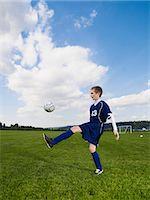 Boy (12-13) kicking football on pitch, side view Stock Photo - Premium Royalty-Freenull, Code: 6106-06990087