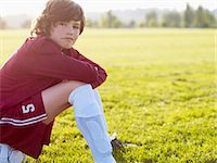 preteen long hair - Boy (10-11) sitting on football in field, side view Stock Photo - Premium Royalty-Freenull, Code: 6106-06990096