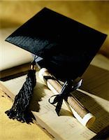 Mortarboard and Diploma on a Ledger Stock Photo - Premium Royalty-Freenull, Code: 6106-06990539