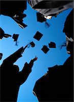 Graduates throwing their mortarboards in the air, low angle view Stock Photo - Premium Royalty-Freenull, Code: 6106-06990546