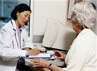 Doctor writing prescription for mature female patient Stock Photo - Premium Royalty-Freenull, Code: 6106-06990597