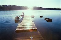Boy sitting on pier in lake, side view Stock Photo - Premium Royalty-Freenull, Code: 6106-06990636