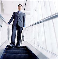 Young businessman riding escalator, holding briefcase, low angle view Stock Photo - Premium Royalty-Freenull, Code: 6106-06993063