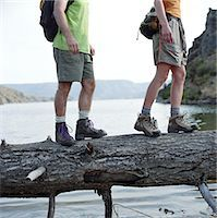Couple walking on log across lake, low section, side view Stock Photo - Premium Royalty-Freenull, Code: 6106-06993564