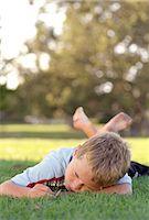 Boy (8-10) lying on stomach in yard Stock Photo - Premium Royalty-Freenull, Code: 6106-06993648