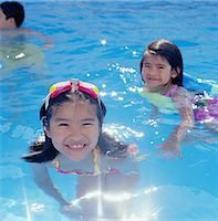 preteen girl wet clothes - Two sisters (4-7) playing in swimming pool, smiling Stock Photo - Premium Royalty-Freenull, Code: 6106-06993761