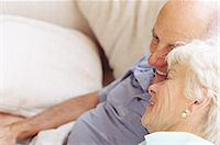 Mature man and woman cuddling on sofa, smiling, elevated view Stock Photo - Premium Royalty-Freenull, Code: 6106-06993905