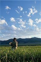 USA, Montana, woman holding fly-fishing pole in tall grass Stock Photo - Premium Royalty-Freenull, Code: 6106-06993949