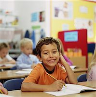 education concept - Children (6-8) sitting at desks in classroom, focus on boy writing Stock Photo - Premium Royalty-Freenull, Code: 6106-06994081
