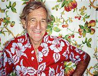 Elderly man standing against fruit-printed wallpaper, portrait Stock Photo - Premium Royalty-Freenull, Code: 6106-06994259