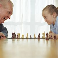 Elderly man and girl (6-8) playing chess, high section Stock Photo - Premium Royalty-Freenull, Code: 6106-06994300