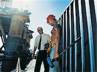 sweaty businessman - Businessman Talking to a Docker by an Oil Rig at the Water's Edge Stock Photo - Premium Royalty-Freenull, Code: 6106-06996164