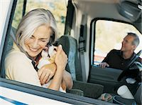 Woman Sitting in a Car and Being Licked by a Dog Stock Photo - Premium Royalty-Freenull, Code: 6106-06996817