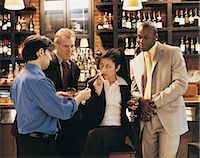 Businessman Lighting a Businesswoman's Cigar in a Bar Surrounded by Other Businessmen Stock Photo - Premium Royalty-Freenull, Code: 6106-06996830