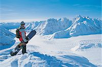 Side View of a Snowboarder Looking at the View of a Snow-covered Mountain Valley Stock Photo - Premium Royalty-Freenull, Code: 6106-06997367