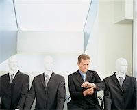 Businessman Checking the Time, Sitting Waiting in a Line With Dummies Stock Photo - Premium Royalty-Freenull, Code: 6106-06997388
