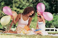 Mother and Daughter Sitting in the Garden Face to Face at a Birthday Party Stock Photo - Premium Royalty-Freenull, Code: 6106-06997626