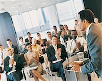 Businessman Standing at a Podium and Giving a Speech to a Conference Room Full of Delegates Stock Photo - Premium Royalty-Freenull, Code: 6106-06998198
