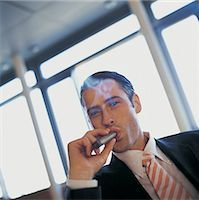 Portrait of a Young CEO Smoking a Cigar Stock Photo - Premium Royalty-Freenull, Code: 6106-06998576