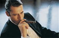 Elevated View of a Young CEO Smoking a Cigar Stock Photo - Premium Royalty-Freenull, Code: 6106-06998584