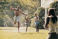 Father and His Sons Running Through a Water Sprinkler in a Garden and their Mother Watching Stock Photo - Premium Royalty-Freenull, Code: 6106-06999339