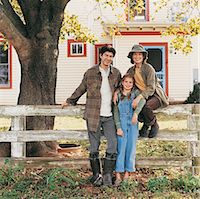 Family of Three Sitting on the Fence Outside Their Home Stock Photo - Premium Royalty-Freenull, Code: 6106-06999421