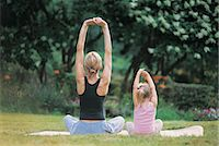 Mother and Daughter Sitting Crosslegged Stretching Arms Above Head, Rear View Stock Photo - Premium Royalty-Freenull, Code: 6106-06999545