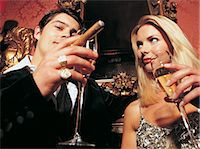 A Couple Drinking Champagne and Smoking a Cigar Stock Photo - Premium Royalty-Freenull, Code: 6106-06999957