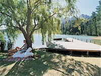 Couple on a Picnic Blanket Under a Tree, Next to a Lake Stock Photo - Premium Royalty-Freenull, Code: 6106-07000158