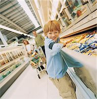 Portrait of a Young Boy Standing in the Frozen Food Aisle of a Supermarket in Front of His Parents With a Shopping Trolley Stock Photo - Premium Royalty-Freenull, Code: 6106-07000924