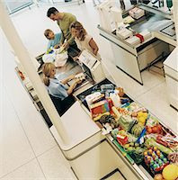 Family of Three Buying Groceries at a Supermarket Checkout Stock Photo - Premium Royalty-Freenull, Code: 6106-07000933