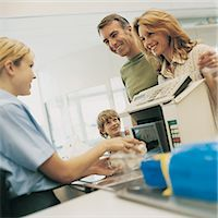 Smiling Family of Three Standing By a Supermarket Checkout Counter Stock Photo - Premium Royalty-Freenull, Code: 6106-07000935