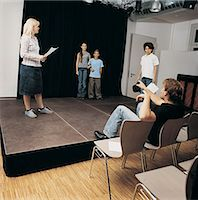Drama Teacher Sits Directing Children as They Rehearse on Stage Stock Photo - Premium Royalty-Freenull, Code: 6106-07001329