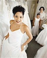 Young Woman Trying on a Wedding Dress in a Bridal Shop. Her Mother and Young Bridesmaid Standing in the Background. Stock Photo - Premium Royalty-Freenull, Code: 6106-07001744