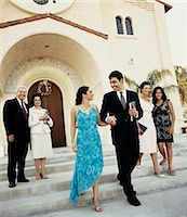 Newlywed Couple Walk Side by Side on the Steps Outside a Church, Their Parents and Relatives Behind Them Stock Photo - Premium Royalty-Freenull, Code: 6106-07001796