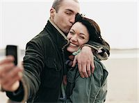 Couple Stand on a Beach Taking a Self-Portrait Stock Photo - Premium Royalty-Freenull, Code: 6106-07001957