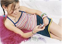 preteen girl pigtails - Young Girl Lying on Cushion and using a Mobile Phone Stock Photo - Premium Royalty-Freenull, Code: 6106-07002069