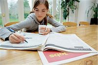 Teenage Girl Sitting Behind a Table Searching for Jobs in a Newspaper Stock Photo - Premium Royalty-Freenull, Code: 6106-07002078