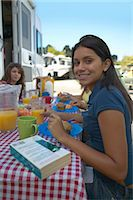 Teenage Girl Sits Eating at a Picnic Table in a Caravan Park Stock Photo - Premium Royalty-Freenull, Code: 6106-07002204