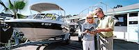 Couple Stand Next to a Motorboat in a Showroom Forecourt Reading a Brochure Stock Photo - Premium Royalty-Freenull, Code: 6106-07002244