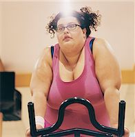 Overweight Woman Riding an Exercise Bike in a Gym Stock Photo - Premium Royalty-Freenull, Code: 6106-07002443