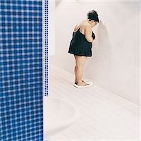 fat woman in bathing suit - Overweight Woman Standing on Scales in a Changing Room Stock Photo - Premium Royalty-Freenull, Code: 6106-07002445