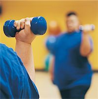 fat man exercising - Close Up of an Overweight Man Weight Training in a Gym Stock Photo - Premium Royalty-Freenull, Code: 6106-07002447